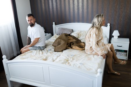 Couple having crisis in bed. Woman and man sitting on bed's edge. Standard-Bild
