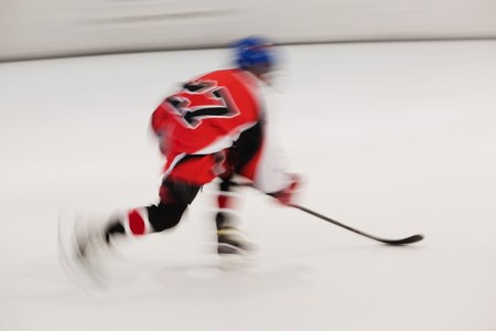Young hockey player in red dress with number 27 in movement, blurry motion on ice stadium Reklamní fotografie
