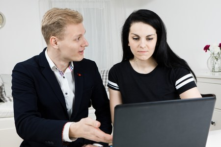 Superiors works with subordinate. Blond man explains to black haired woman, disputing emotionally