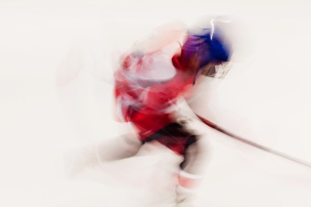 Hockey player in red dress and blue helmet in movement, blurry motion on ice stadium