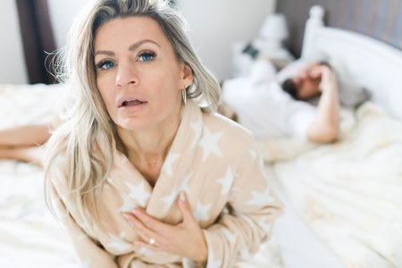 Couple having crisis in bed. Woman sitting on bed's edge, man in background.