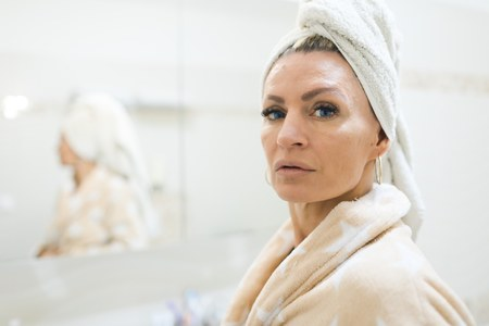 Woman having towel on head after taking a shower. Skin care at any age on daily basis