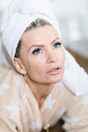Attractive woman with blue contact lenses with towel on head after relaxation in bedroom. Stock Photo