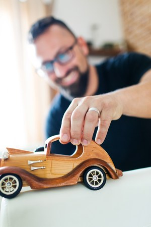 Back in childhood, man playing with wooden toy car - classical toys Stock Photo