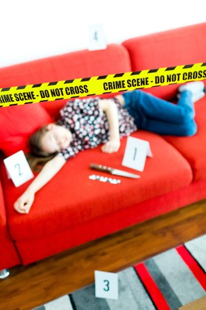 Young victim in blue jeans laying on red sofa - crime scene with knife and yellow gap do not cross.