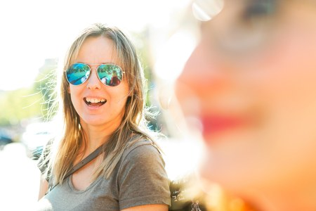 Woman in green T-shirt smiling in background second woman in out of focus foreground.