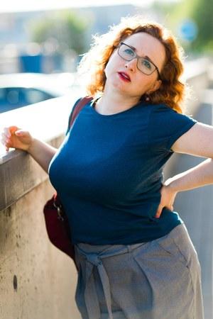 Frau auf der Straße mit plötzlichen Rückenschmerzen - Geste von Rückenschmerzen
