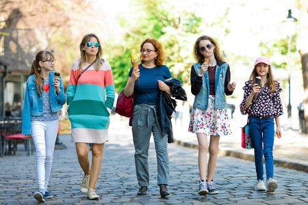 Group of fashion girls walking through downtown, mothers and daughters together on a trip having ice cream. Stok Fotoğraf