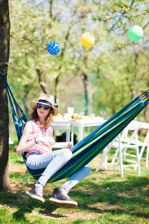 Teen girl with sunhat sitting in hammock on garden party and eating cake Stock Photo