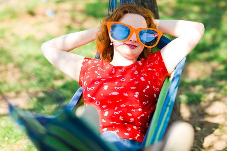Woman in red dress and big funny sun glasses lying on hammock - summer party Stock Photo