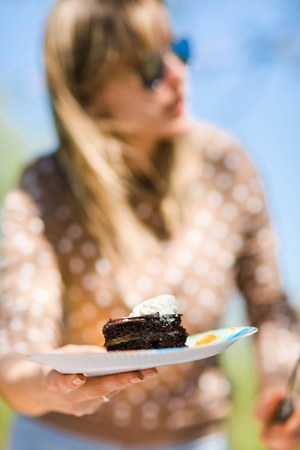 Beautiful woman offering piece of birthday cake op paper plate - summer garden party outside