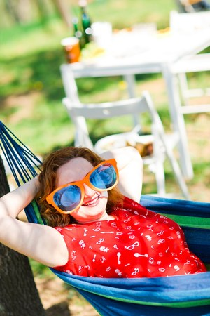 Woman in red dress and big funny sun glasses lying on hammock - summer garden party Stok Fotoğraf