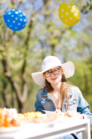 Teen aged girl in white sunhat sitting by table on birthday garden party - sunny day
