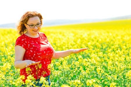 Attractive woman in red dress posing in oilseed rape field - feeling positive energy