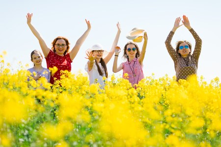 Two attractive women and three young girls posing in oilseed rape field - feeling positive energy