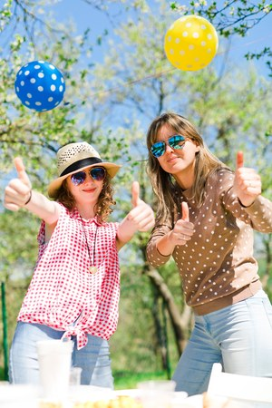 Mother with daughter on birthday garden party during summer sunny day - showing thump up together Stock Photo
