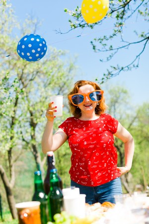 Woman posing in red dress and big funny sun glasses on garden party - summer picnic Stock Photo