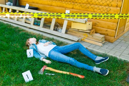 Crime scene in backyard with body of victim - ax as weapon - do not cross yellow gap