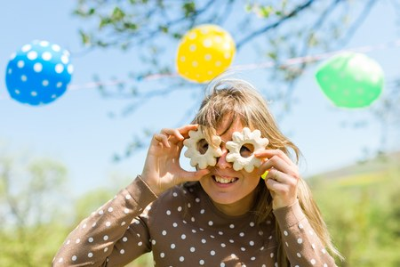 Woman making fun - glasses from home made cakes - summer garden party