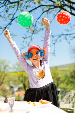 Young girl in funny big sun glasses on garden party - having fun on summer picnic - hands up