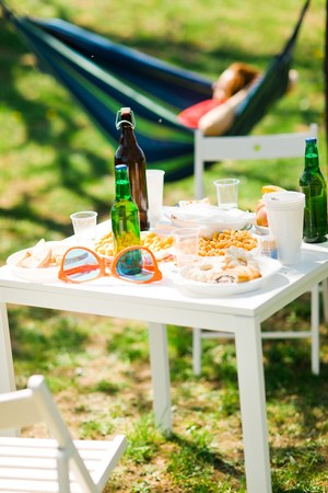 Table with bottles of beer and food on summer garden party - woman in hammock in background