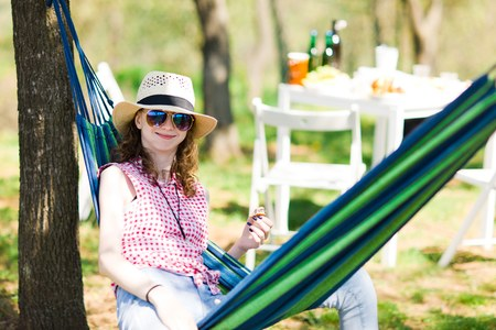 Teen girl with sunhat sitting in hammock on garden party and eating cake - summer sunny day