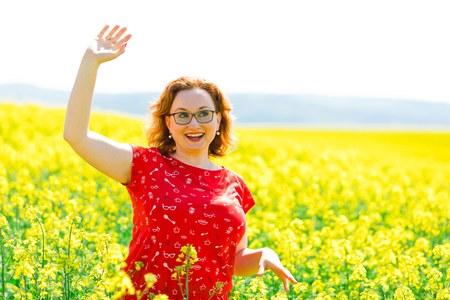 Attractive woman in red dress in oilseed rape field - waving with hand - gesture hello there