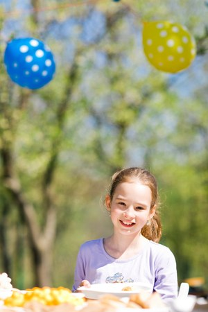 Teen aged girl sitting by table on birthday garden party - sunny day
