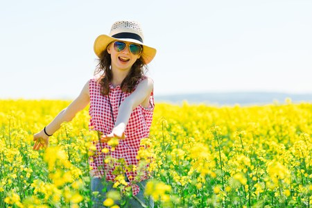 Young girl in red checkered dress and sunhat posing in oilseed rape field - having a fun