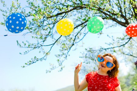 Woman posing in red dress and big funny sun glasses on garden party - showing on balloons