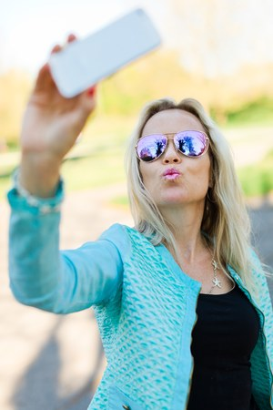Blond woman with sun glasses making selfie with smart phone.