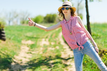 Young girl with sunhat hitchhiking on of road - hot summer day in nature