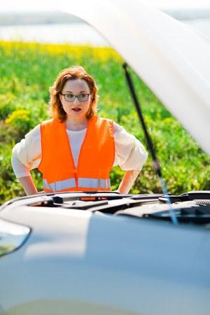A woman in orange vest open car bonnet of broken car - trying to solve problem Stock Photo