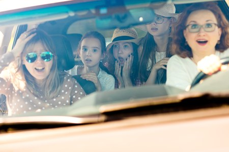 Two mothers with three daughters scared in car - looking amazed by incoming accident - fear behind the wheel