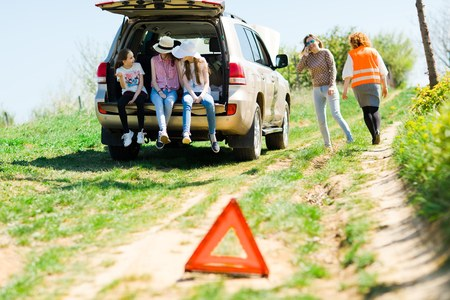 A breakdown triangle stands near a broken car - of road - family behind looking for help