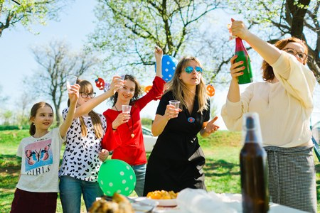Toast with child champagne on birthday garden party - plastic cups Stock Photo