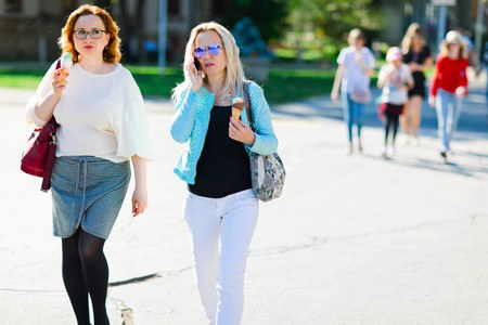 Two attractive women walking downtown and eating ice cream - summer street life Stock Photo