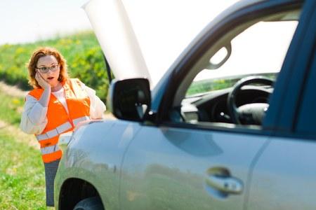 A woman in orange vest open car bonnet of broken car - thinking how to solve problem
