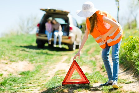 Young girl in orange vest set up breakdown triangle stands near a broken car - of road