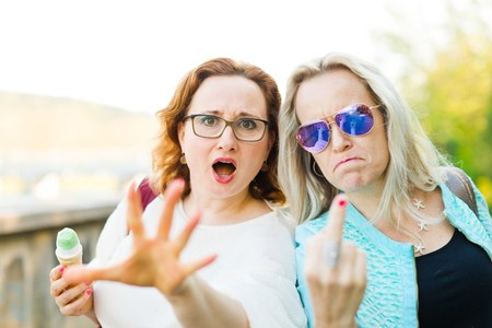 Two attractive women walking downtown and eating ice cream - showing rude gestures with middle finger Stock Photo
