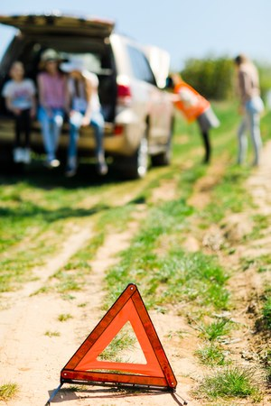 A breakdown triangle stands near a broken car - of road - family with children behind looking for help