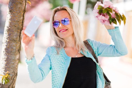 Blond woman under cherry blossom taking selfie - spring in the city