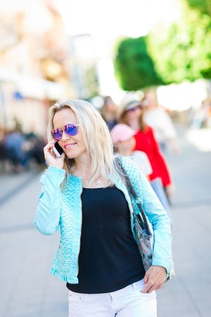 Attractive blond woman in sun glasses walking downtown and using cell phone - street life Stock Photo