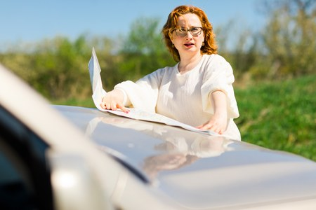 Attractive woman checking position in paper map on bonnet of the car - lost on trip in nature Stock Photo