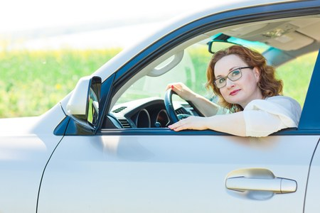 Attractive woman posing in car on drivers seat - open window