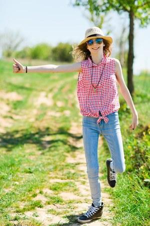 Young girl with sunhat and checkered shirt hitchhiking on of road - hot summer day