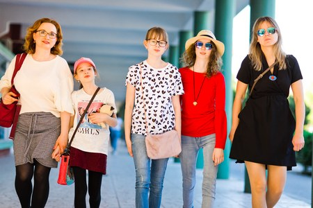 Young girls and women on shopping trip - mothers with daughters walking the city