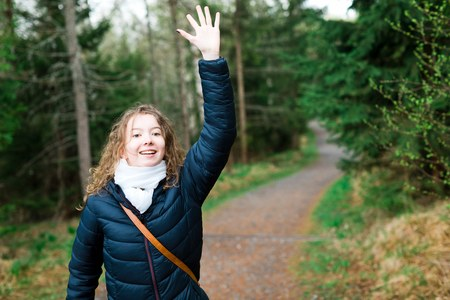 Young girl tourist in black jacket on walking trail in th forrest - saluting with hand Stock Photo