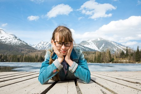 Young girl is lying on wooden boards in mountains near lake - thoughtful gesture Stock Photo