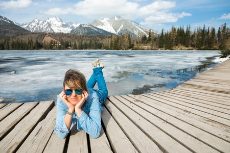 A woman in jeans lying on wooden terrace by frozen mountains lake - spring time coming